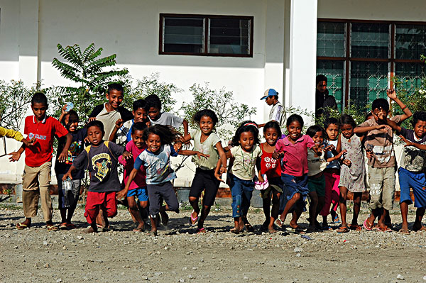 2 crossing hands of 2 refugee children with smiling faces in the background, dili, east timor